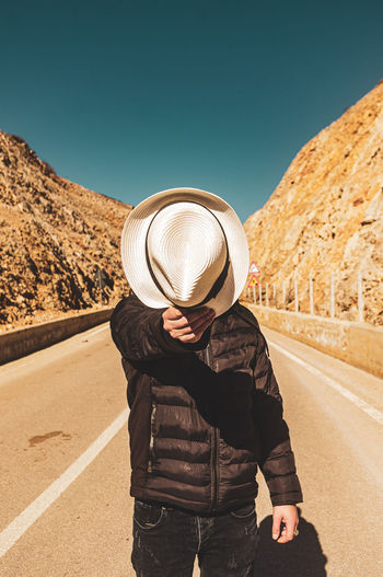 Man wearing hat standing by road against clear sky