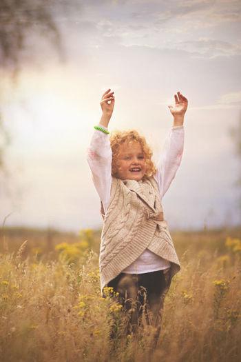 Smiling Girl Standing On Field Against Sky