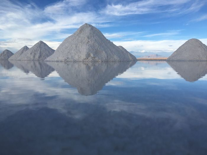 Salt By Calm Lake Against Sky At Salar De Uyuni