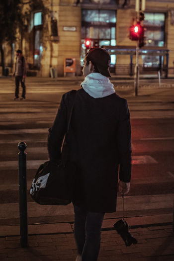 Rear view of woman walking on footpath at night