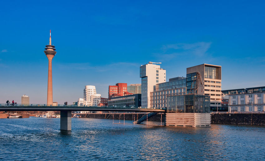 Duesseldorf, Germany - February 27, 2016: view on TV-Tower, marina and famous buildings at new media harbor of Duesseldorf with blue sky and sunny weather Architecture Built Structure Building Exterior City Sky Water Building Tower Tall - High Office Building Exterior Travel Destinations Waterfront Travel Tourism Connection Nature Blue Skyscraper Bridge - Man Made Structure No People Spire  Modern Outdoors Cityscape