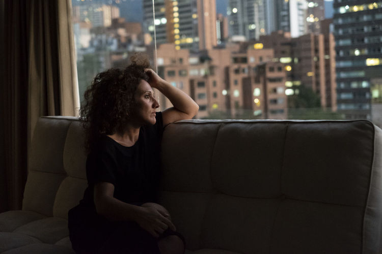Thoughtful woman sitting on sofa in city
