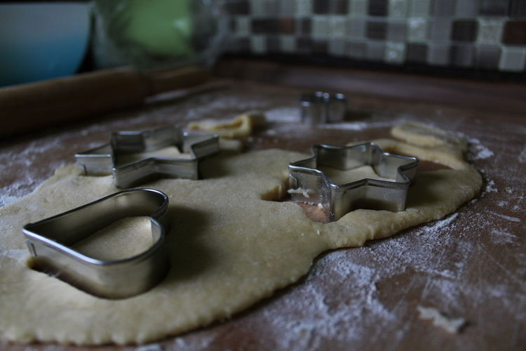 Close-Up Of Pastry Cutters On Dough At Table