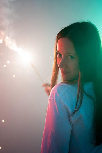 Portrait of woman holding illuminated sparkler