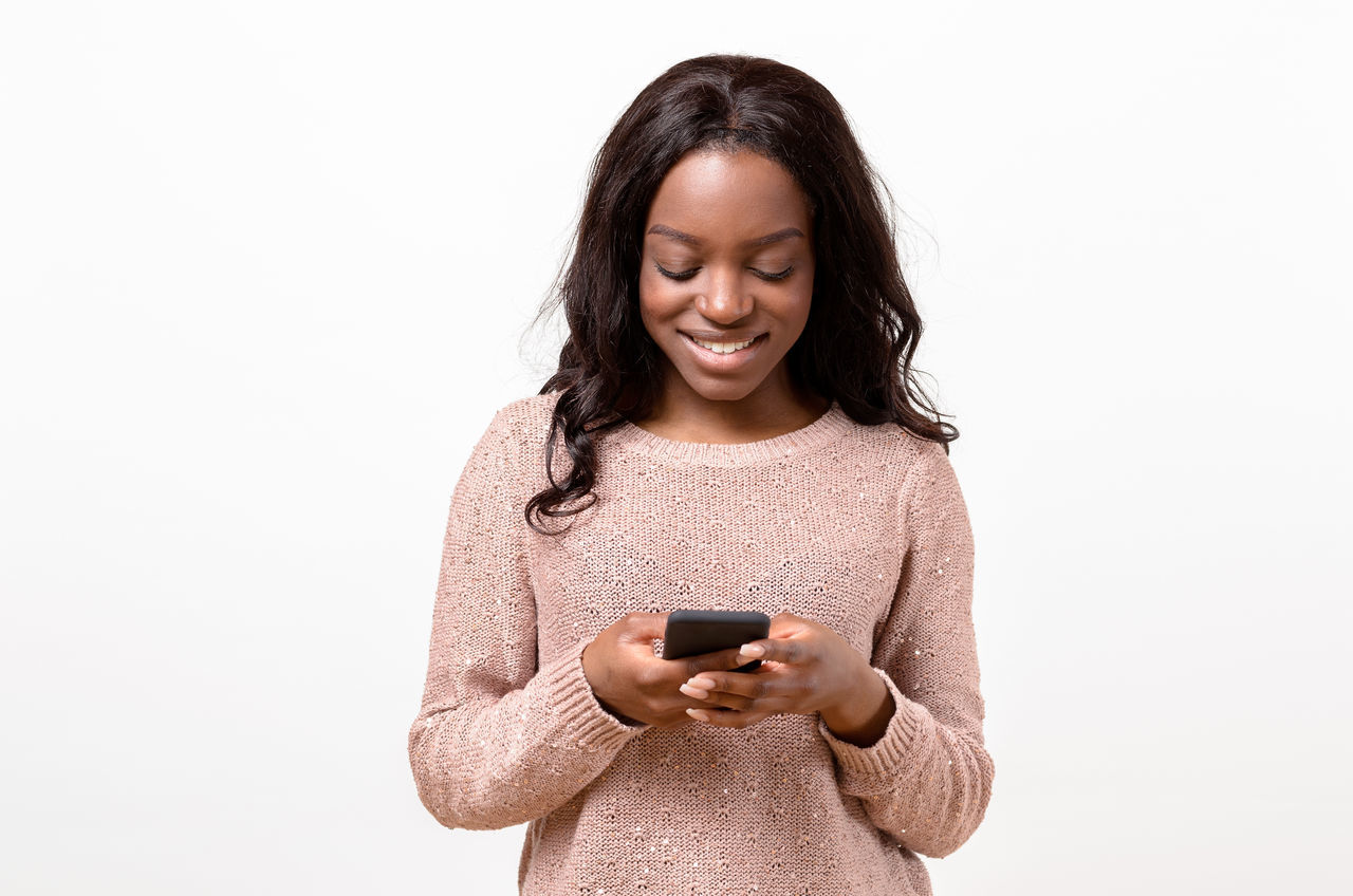 Smiling Young Woman Using Phone Against White Background