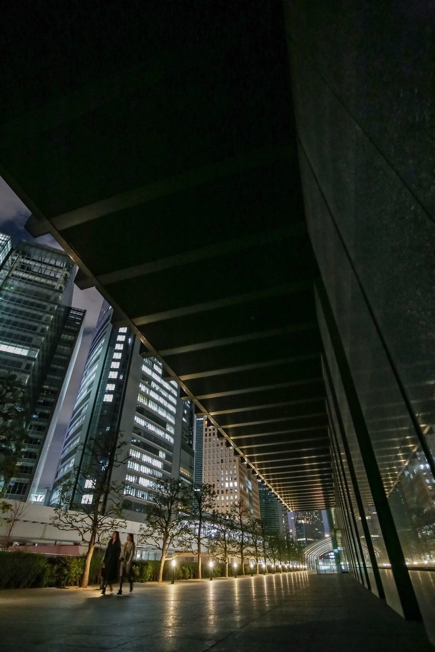 architecture, built structure, building exterior, city, night, illuminated, building, modern, outdoors, people, incidental people, office building exterior, office, nature, city life, connection, two people, walking, women, low angle view, skyscraper