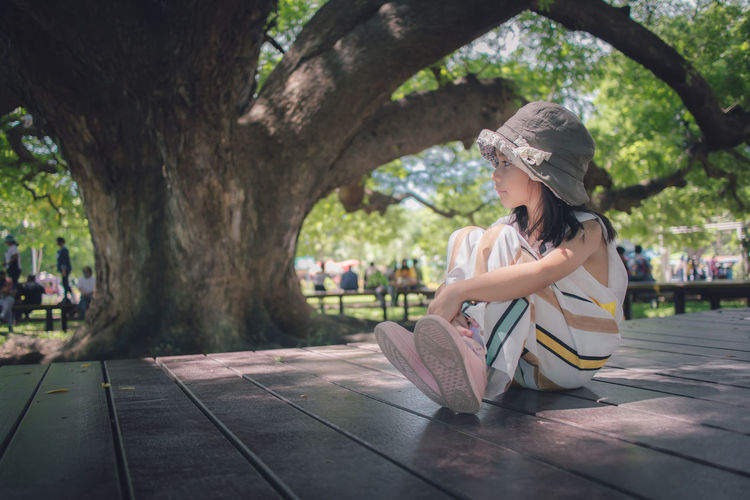 Woman sitting by book against tree