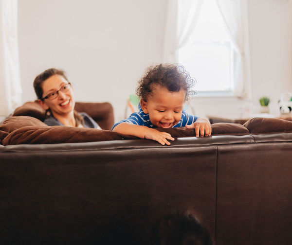 Smiling mother with kids sitting on sofa at home