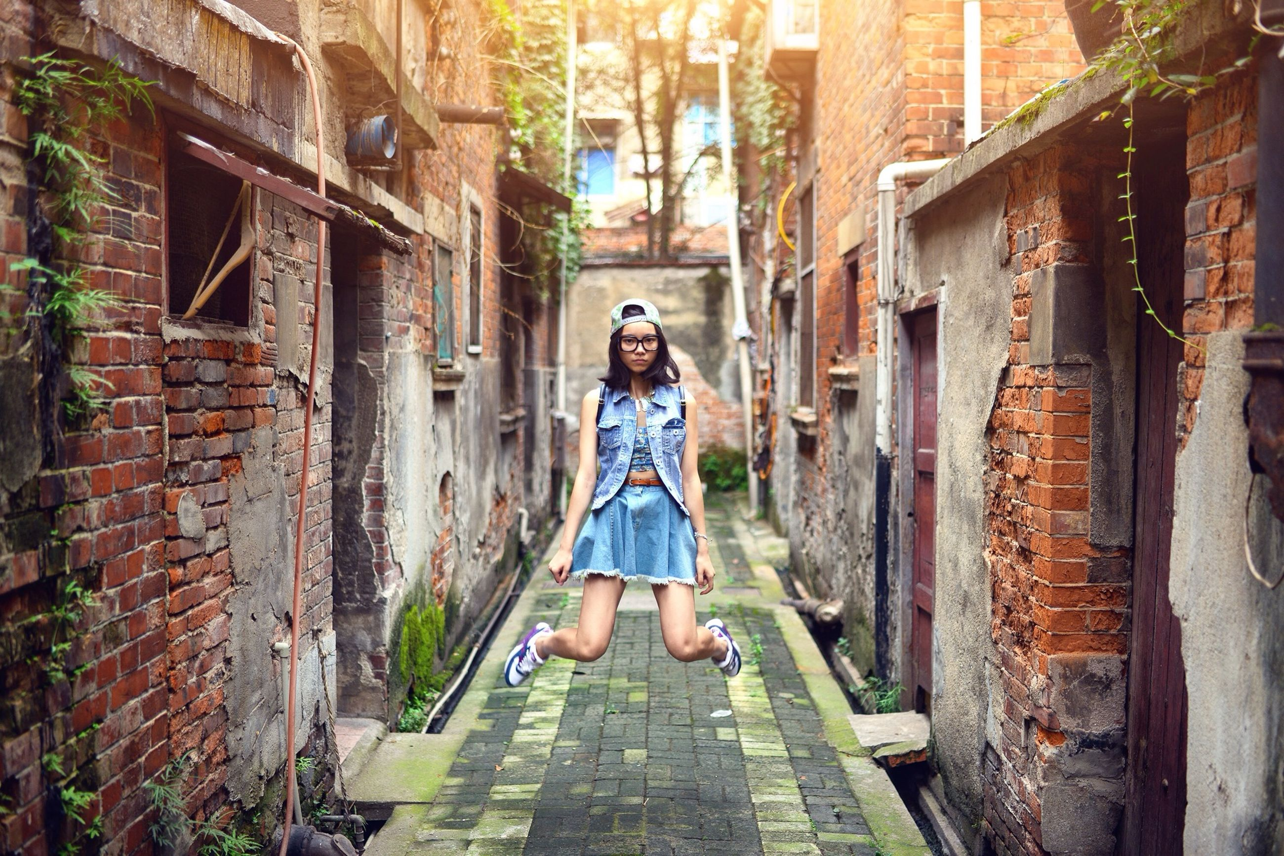 architecture, building exterior, built structure, casual clothing, full length, lifestyles, young adult, standing, person, building, wall - building feature, leisure activity, brick wall, stone wall, old, residential structure, house, young women