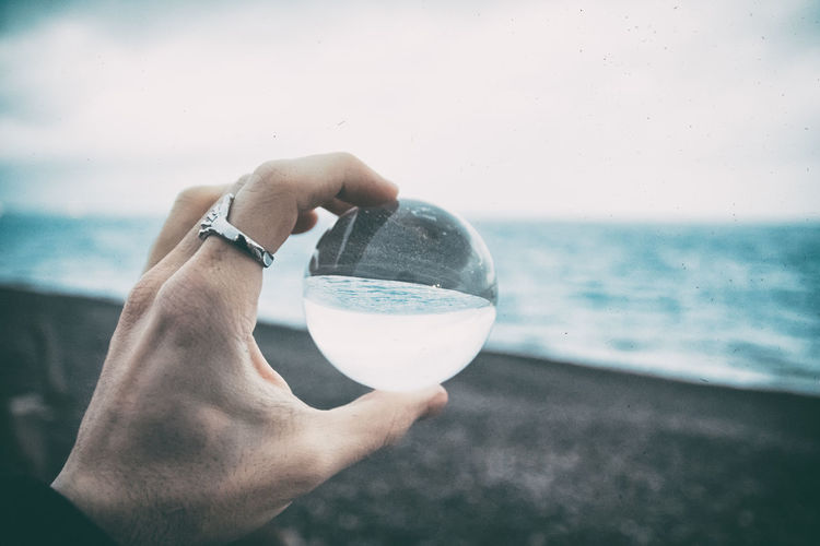 Cropped Hand Holding Crystal Ball At Beach