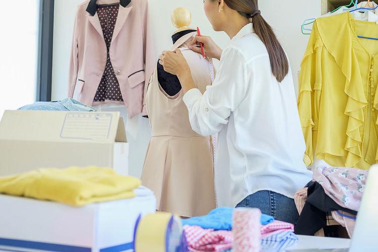 Rear view of fashion designer taking measurement of garment
