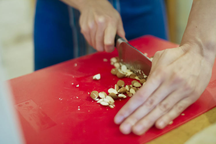 Midsection of person chopping almonds on red cutting board