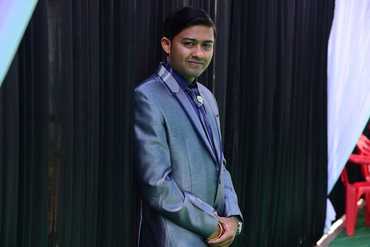 Portrait Of Smiling Young Man Wearing Suit While Standing Against Curtains
