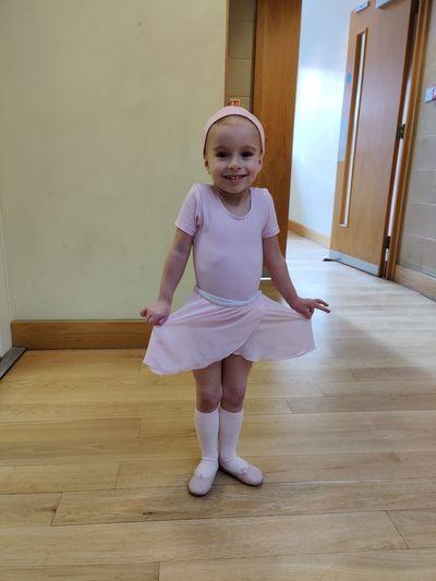 Full length portrait of cute ballerina girl