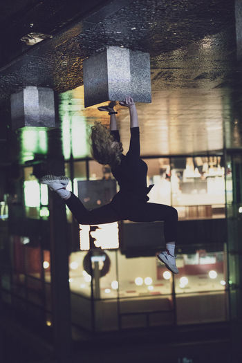 Upside down image of woman doing handstand on street at night