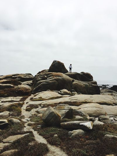 Rear view of woman standing on boulder against sky