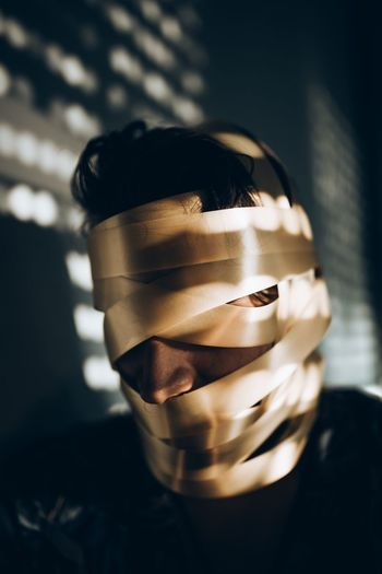 Close-up of man with face covered by tape