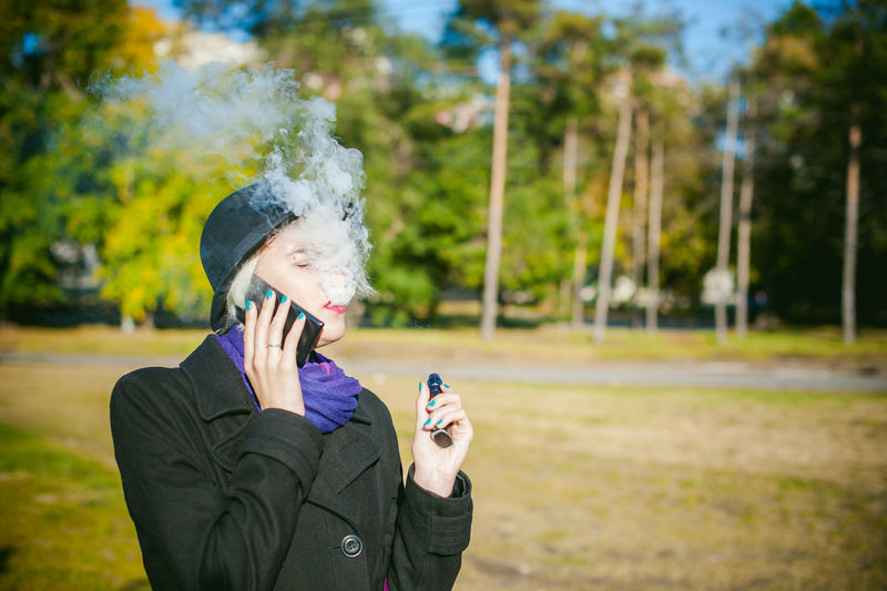 Young Woman Talking On Mobile Phone While Smoking At Park