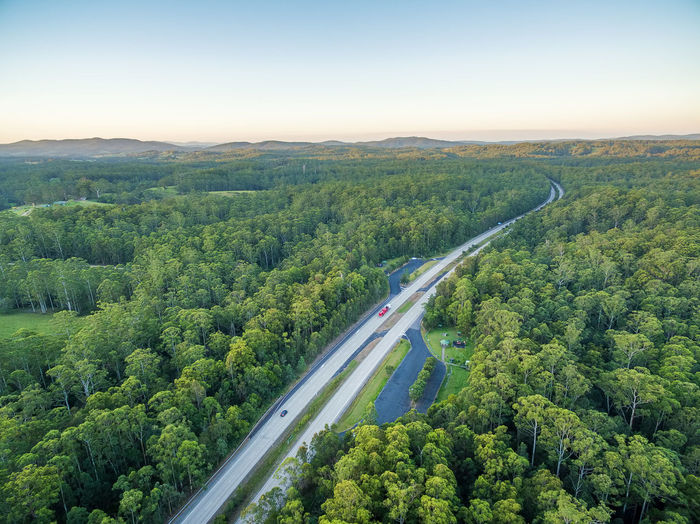 Aerial view of road amidst green landscape against sky during sunset