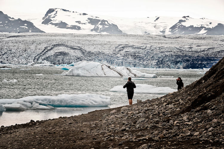Two men walk along the shore of Jokulsarlon with mountains and glaciers in the background. Adult Astrology Sign Cold Temperature Day Glacier Glaciers Icebergs Iceland Jökulsárlón Landscape Mountain Mountain Range Outdoors People Snow