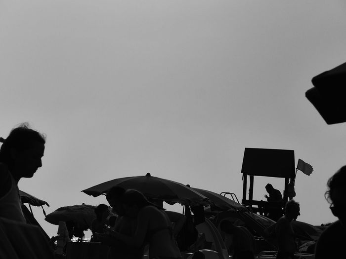 People holding umbrella against clear sky