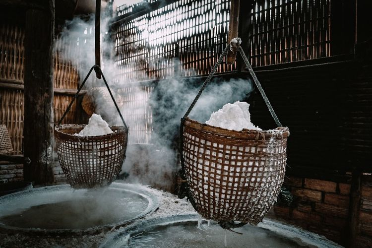 Rice in wicker baskets above water filled container with steam