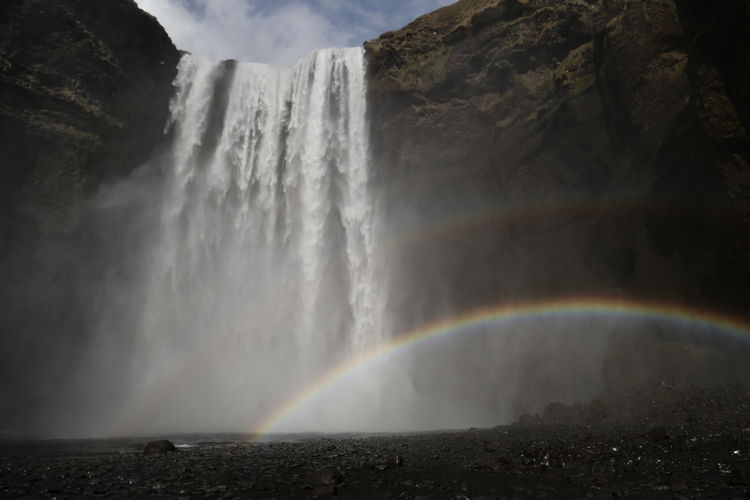 Scenic view of rainbow against waterfall and mountain