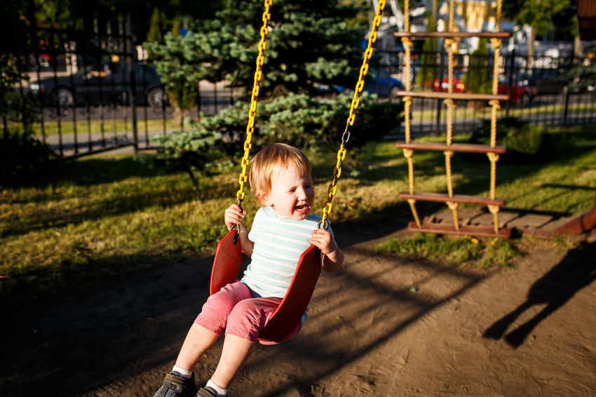 Little girl is swinging at a playground when the sun is setting. Happiness and family concept Childhood Cute Day Family Full Length Girl Girls Happiness Happy Child  Having Fun Joy Kid Leisure Activity Love Love ♥ One Person Outdoors People Playing Real People Smiing Summer Sun Sunset Swing