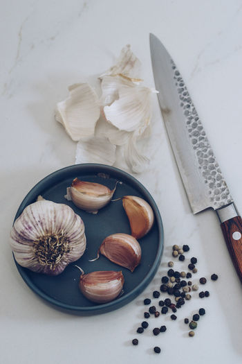 Garlic pepper corns and a knife on white marble