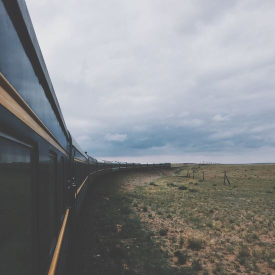 Train Passing By Field Against Cloudy Sky