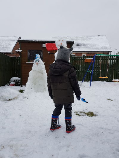 Building an army... Child Kid Snowman Built Cold Winter Garden Childhood Memories Winter Full Length Snow Cold Temperature Rear View One Person Warm Clothing People Day Outdoors Standing Nature