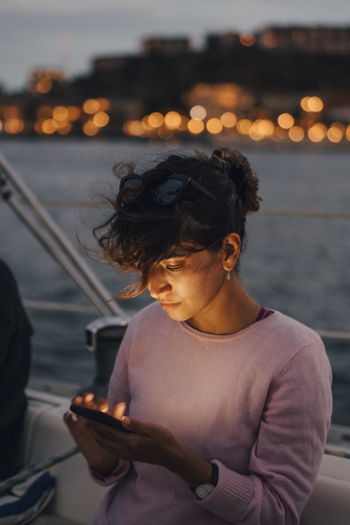 Woman sitting on boat at sea during sunset