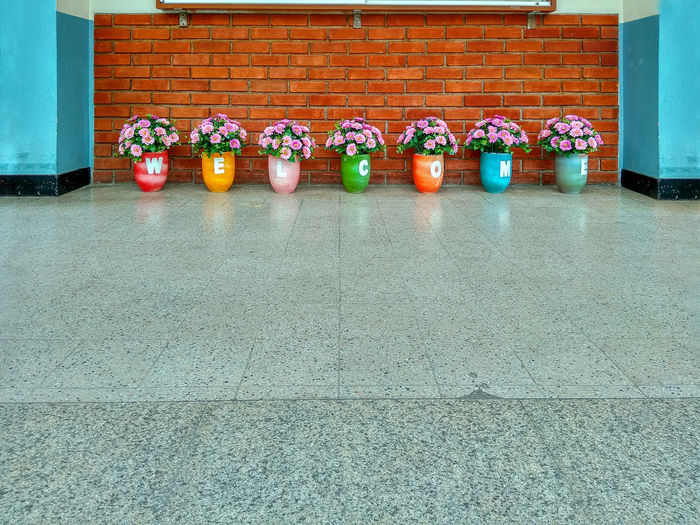 Flower pot with welcome Side By Side No People In A Row Architecture Tile Built Structure Day Wall - Building Feature Flooring Multi Colored Absence Order Food And Drink Food Tiled Floor Outdoors Arrangement Orange Color Footpath Building Exterior Welcome Pot