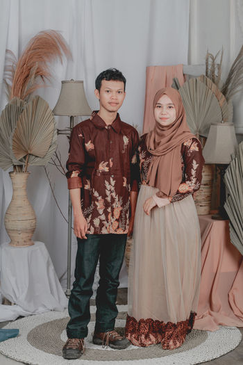 Portrait of young couple standing at home