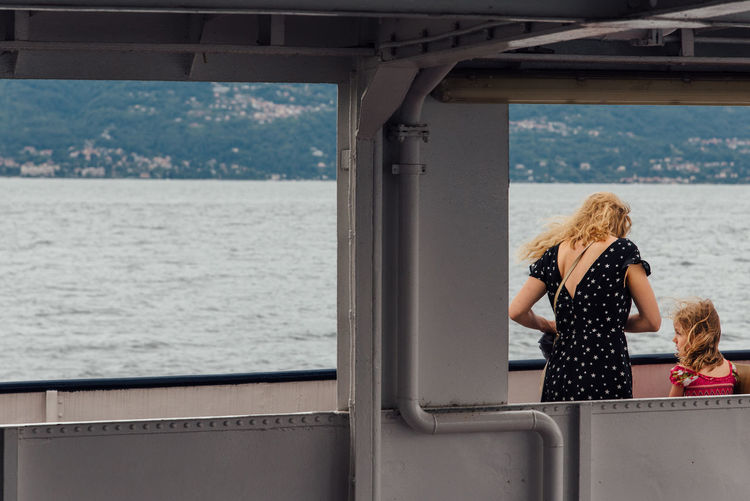 Rear View Of Mother And Daughter Standing On Ferry Boat In Sea