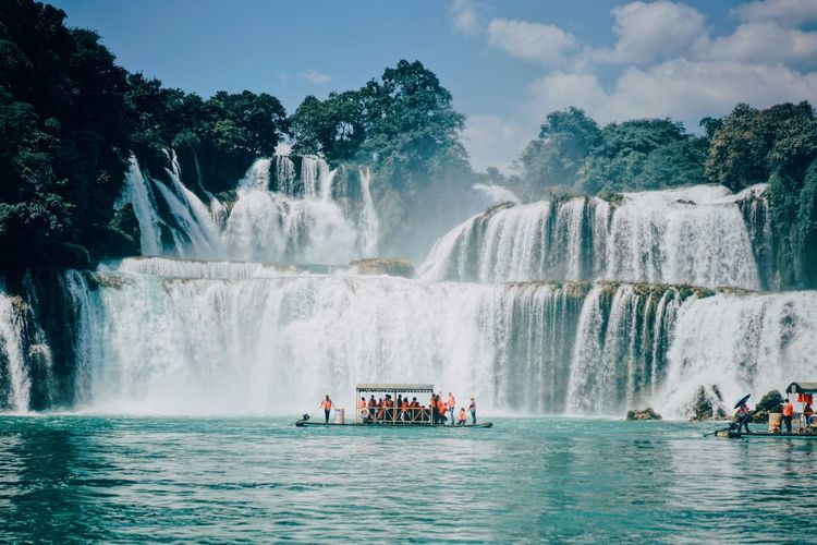 People In Boat Against Waterfall