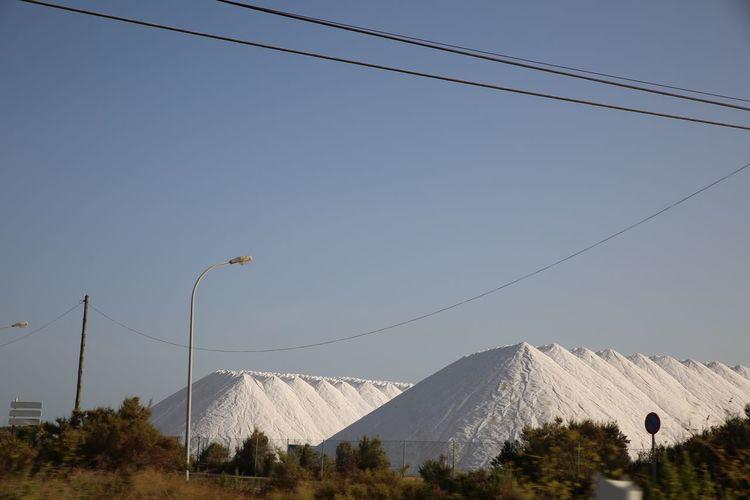 View of salt pans against clear blue sky