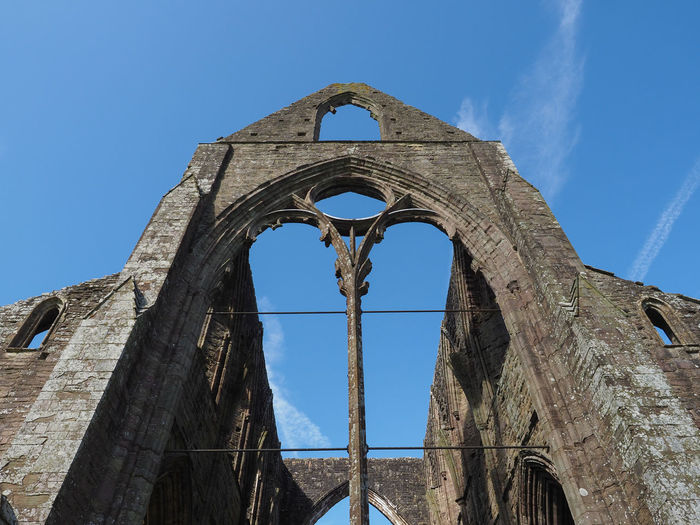 Low angle view of old ruin building against blue sky