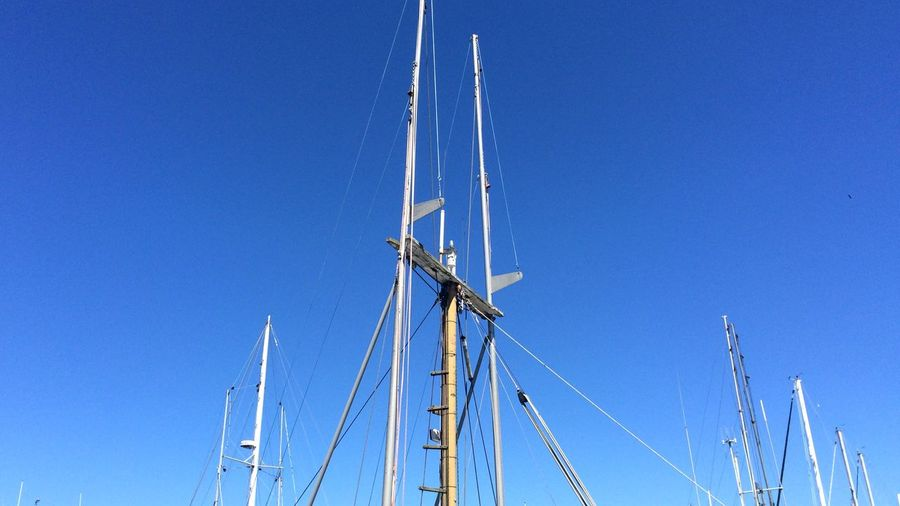 Low Angle View Of Sailboat Masts Against Blue Sky