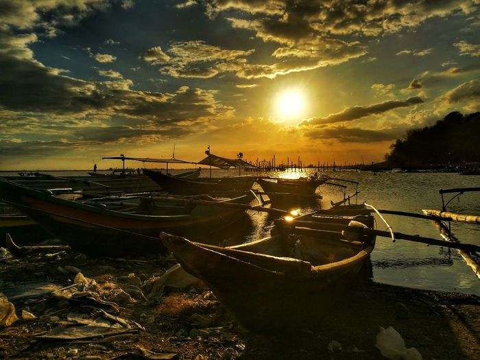 Boats moored on sea against sky during sunset