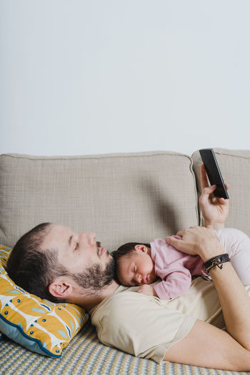 Midsection of man using mobile phone while relaxing on bed