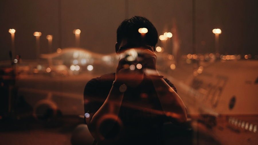 Man photographing through camera reflecting on window at night