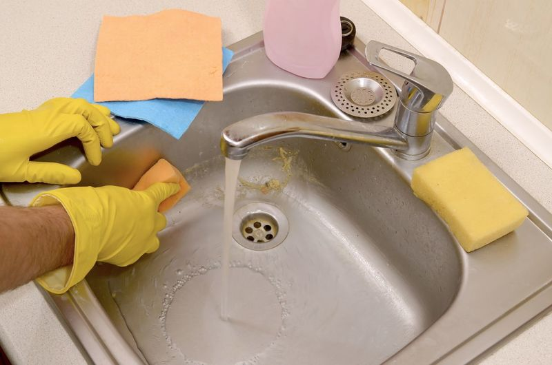 High angle view of man cleaning dirty sink at kitchen