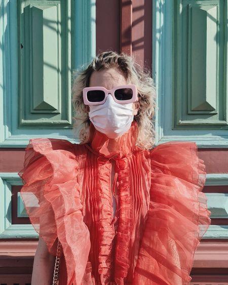 Portrait of woman wearing sunglasses standing by window