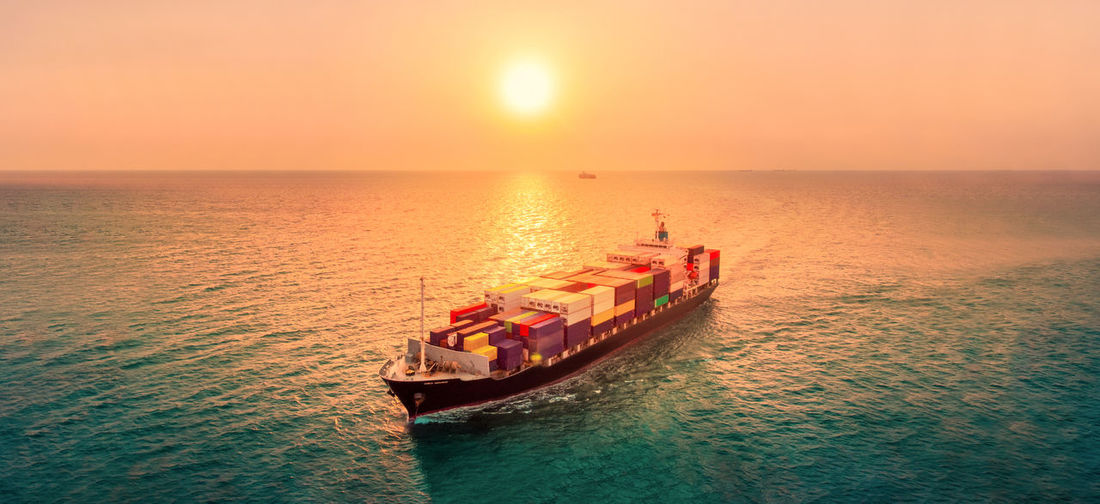 Smart cargo container ship at sunset import export container concept freight shipping sea port.