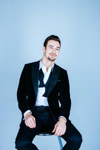 Portrait of businessman sitting on stool against blue background