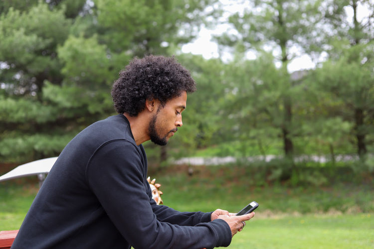 Side view of young man using mobile phone