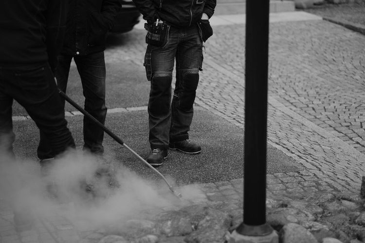 Low Section Of Male Workers Spraying Smoke On Street
