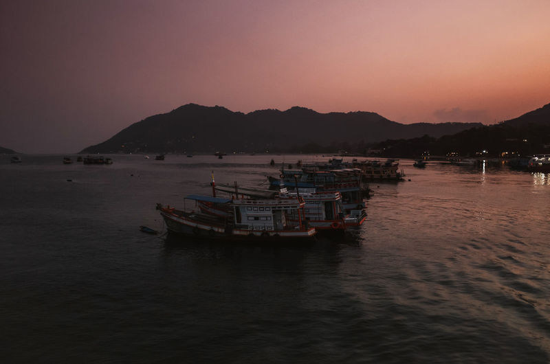 tranquil scene of fishing boats during sunrise in a bay in Koh Tao, Thailand Thailand Transportation Nautical Vessel Water Mode Of Transportation Sky Sea Mountain Sunset Waterfront Scenics - Nature Beauty In Nature Nature No People Moored Mountain Range Clear Sky Dusk Tranquil Scene Travel Outdoors Fishing Boat Passenger Craft Fishing Industry Sunrise