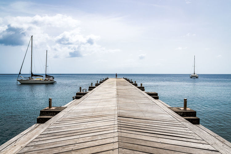 Sailboats On Pier By Sea Against Sky
